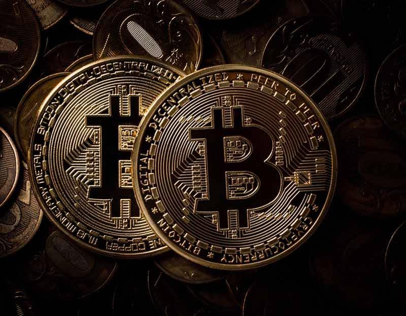deux bitcoins en monnaie dans une image aux tons foncés